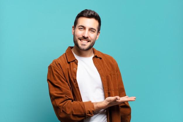 Bell'uomo biondo adulto che sorride allegramente, si sente felice e mostra un concetto nello spazio della copia con il palmo della mano