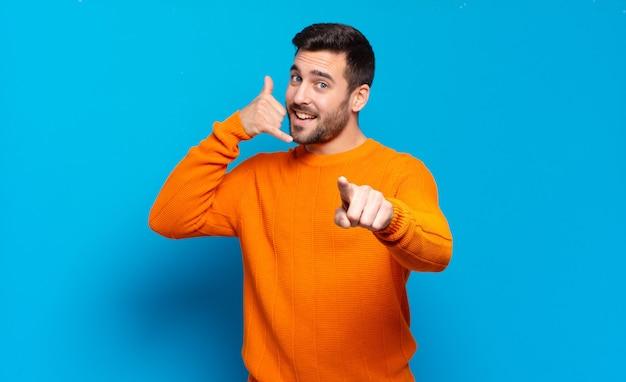 Bell'uomo biondo adulto che sorride allegramente e indica la telecamera mentre fa una chiamata dopo un gesto, parlando al telefono