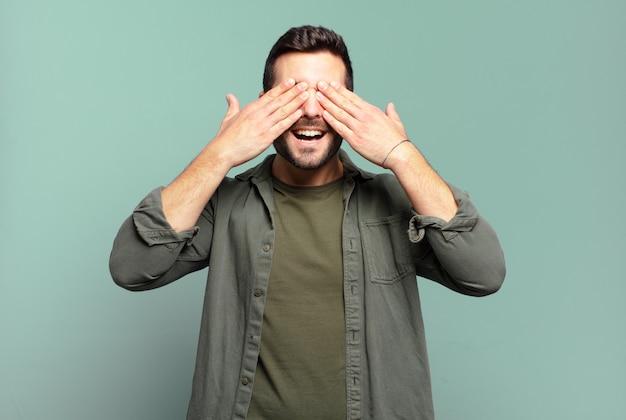 Bell'uomo biondo adulto che sorride e si sente felice, copre gli occhi con entrambe le mani e aspetta un'incredibile sorpresa