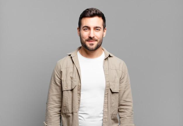 Uomo biondo adulto bello che sorride positivamente e con fiducia, sembra soddisfatto, amichevole e felice