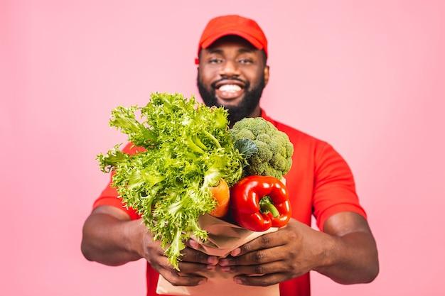 Uomo di consegna afroamericano bello che trasportano scatola del pacchetto di generi alimentari alimentari dal negozio