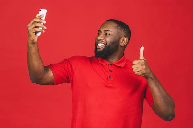 Uomo afroamericano bello che utilizza smartphone per scattare foto selfie e sorridente.