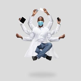 Bel medico africano, uomo multi-armato che levita isolato su sfondo grigio studio con attrezzatura. concetto di occupazione professionale, lavoro, lavoro, medicina, assistenza sanitaria. multi-task come shiva.
