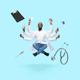 Bel medico africano multiarmed uomo levitante isolato su blu studio background