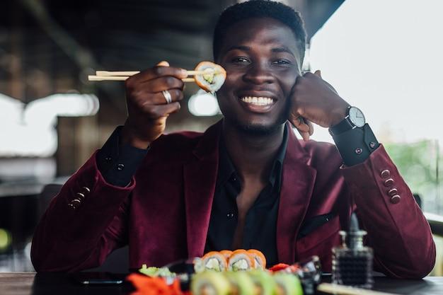 Bel maschio africano con piatto di sushi sulla terrazza estiva. sushi di gusto di uomo d'affari felice.