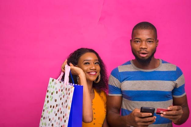Bell'uomo africano che fa shopping per il suo amico online mentre tiene in mano le borse della spesa.