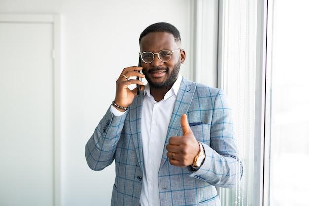 Bell'uomo africano con il telefono cellulare con il gesto della mano