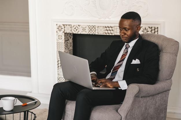 Uomo d'affari afroamericano bello in vestito classico sta usando un laptop e sta sorridendo mentre lavorava in ufficio