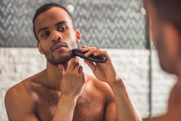L'uomo afro bello sta radendosi usando un rasoio elettrico
