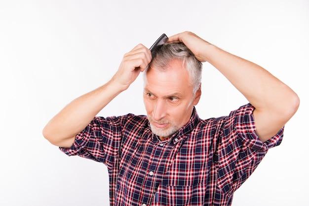 Uomo invecchiato bello che pettina i capelli isolati