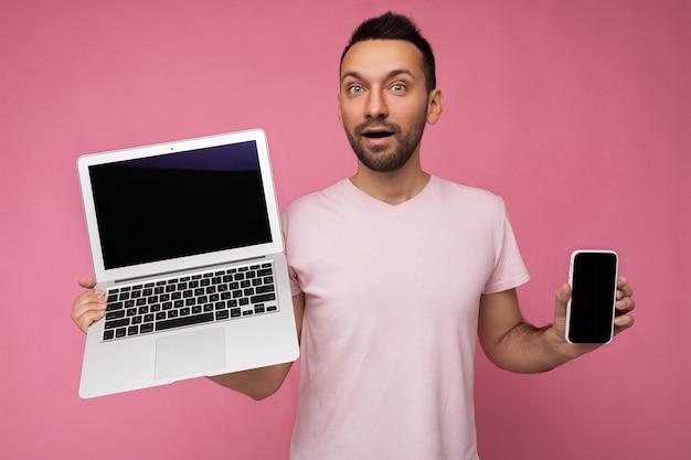 Bell'uomo stupito con la bocca aperta che tiene il computer portatile e il telefono cellulare che guarda l'obbiettivo in t-shirt sulla superficie rosa isolata