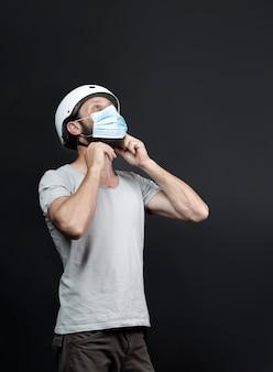 Un bell'uomo barbuto americano che lavora nella consegna dei pacchi, indossa un casco da bici con una maschera chirurgica per essere al sicuro durante la pandemia di coronavirus. motociclista russo fissaggio casco da bicicletta su sfondo grigio.