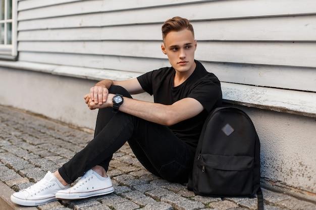Bell'uomo americano con un'acconciatura alla moda in una maglietta nera alla moda in jeans alla moda in scarpe da ginnastica bianche