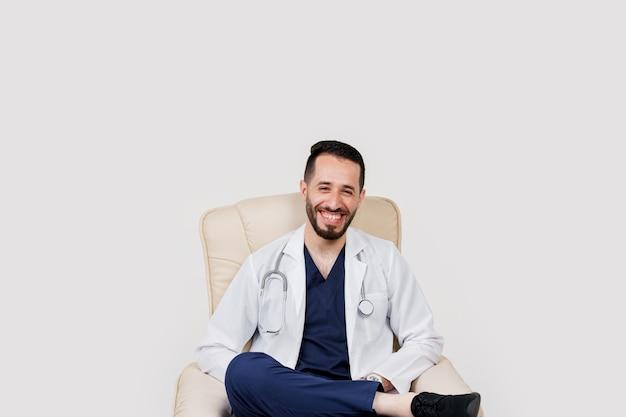 Sorrisi di bel medico chirurgo arabo studente barbuto con stetoscopio in abiti medici in poltrona su sfondo tranciato.