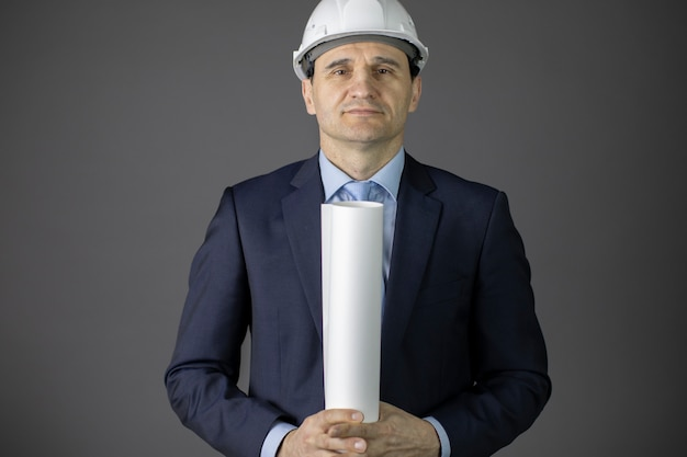 L'architetto bello in cappello duro tiene il rotolo del modello esamina con confidenza la macchina fotografica
