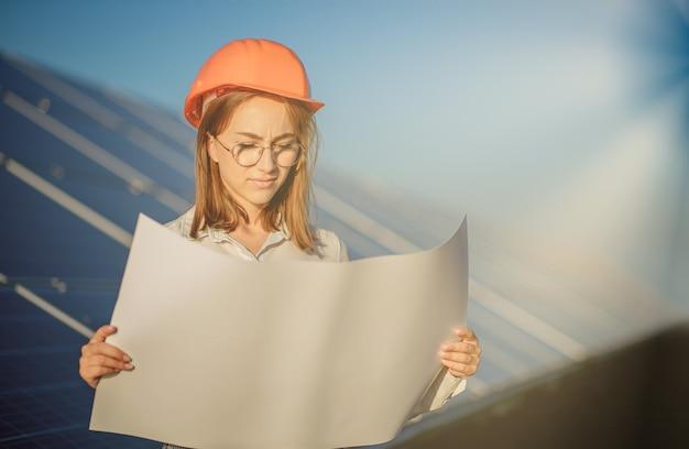 Bello architetto donna esaminando una bozza di mappa o piano di progetto blueprint