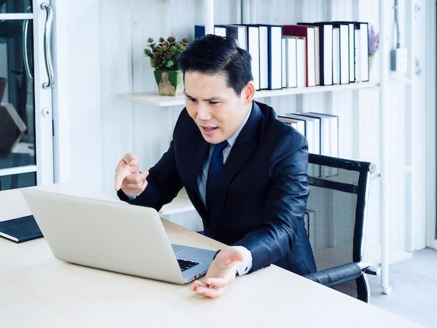 Uomo d'affari asiatico bello in videochiamata tuta, lamentandosi con un collega tramite computer portatile in riunione di lavoro online, videoconferenza