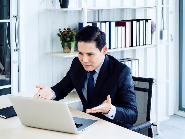 Uomo d'affari asiatico bello in videochiamata tuta, spiegando al collega tramite computer portatile in riunione di lavoro online, videoconferenza