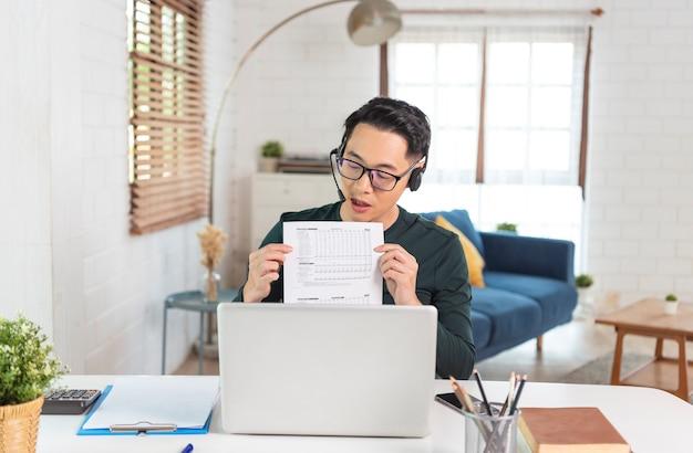 L'uomo d'affari asiatico bello indossa le cuffie che lavorano a distanza da casa. è webinar in videoconferenza.