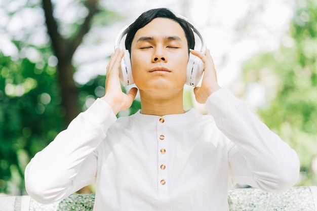 Uomo asiatico bello che gode della musica al parco