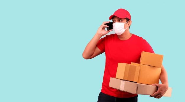 Uomo asiatico bello in berretto rosso, indossando maschera per la protezione da germi e virus. in sospeso con la scatola del pacco postale in scatole di cartone isolato tenendo il telefono cellulare in studio