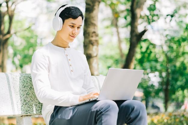 Uomo asiatico bello che si siede facendo uso del computer portatile per lavorare al parco