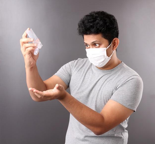 Bell'uomo asiatico con gel per alcol e con maschera medica, consiglia la prevenzione di virus e varie malattie.