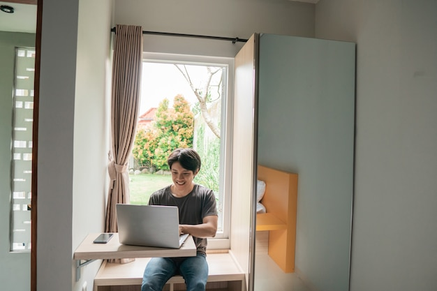 Progettista moderno asiatico bello dell'uomo che lavora a casa utilizzando il computer portatile a casa