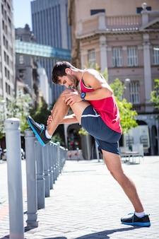 Atleta bello che fa gamba che si estende su un palo