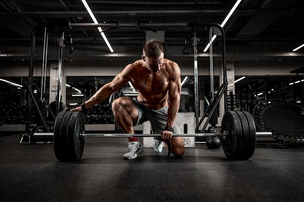 Atleta bello in buona forma che prepara il bilanciere per l'allenamento, raggiungendo il successo attraverso un allenamento testardo e duro.