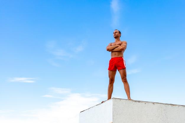 Atleta bello shirtless young man si erge su una roccia contro il cielo
