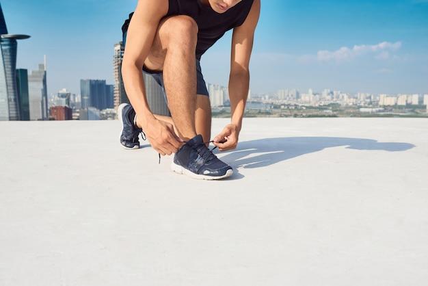 Bello atleta che si allaccia i lacci delle scarpe in una giornata di sole