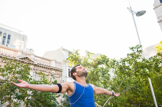 Atleta bello con le braccia tese