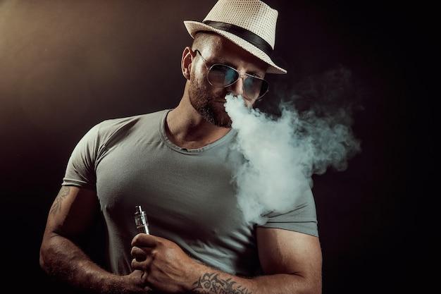 Bell'uomo atletico sta svapando una sigaretta sul muro nero