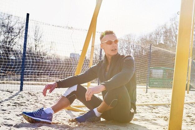 Bell'uomo atletico seduto sul campo di sabbia per il beach soccer
