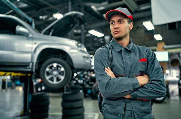 Bel meccanico di servizio auto in uniforme è in piedi sullo sfondo dell'auto con il cofano aperto e guarda lontano. riparazione e manutenzione auto.