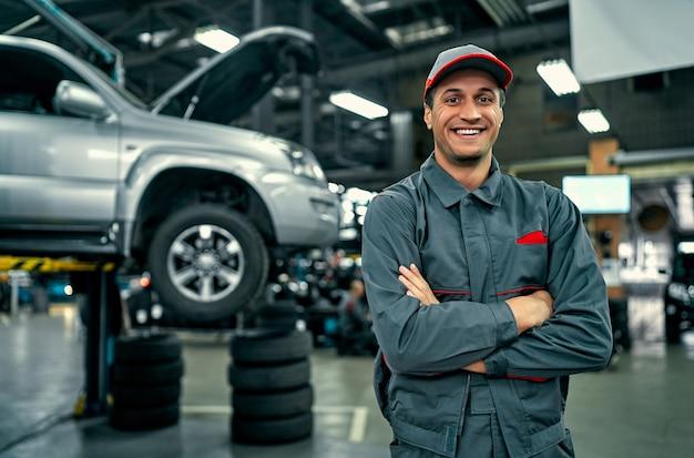 Bel meccanico di servizio auto in uniforme è in piedi sullo sfondo dell'auto con il cofano aperto, sorridendo e guardando la fotocamera. riparazione e manutenzione auto.