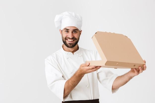Bell'uomo fornaio in uniforme da cuoco che sorride e tiene in mano una scatola per pizza isolata su un muro bianco