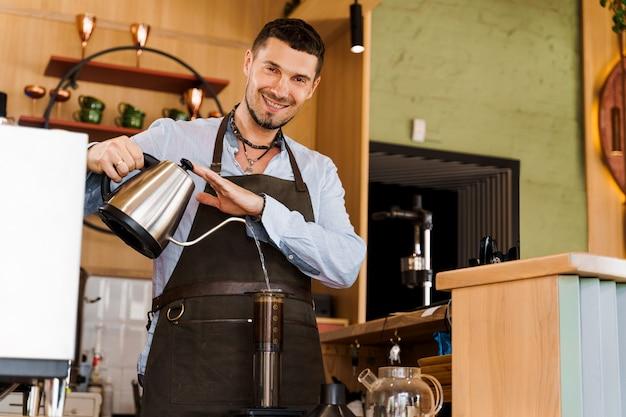 Bel barista versa acqua calda in aeropress con caffè e guarda a porte chiuse e sorride nella caffetteria
