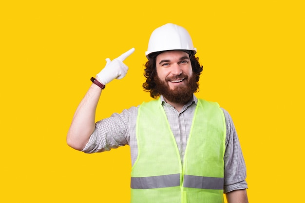 Uomo bello architetto barbuto che punta al cappello duro