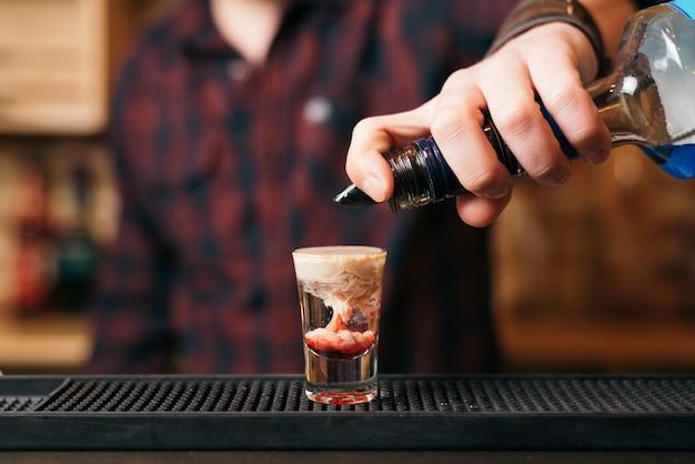 Il barista barbuto bello sta preparando un cocktail al cervello di scimmia nel night club. messa a fuoco selettiva sul vetro.