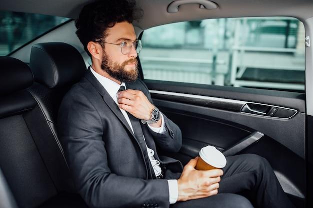 Bello uomo d'affari barbuto seduto con il caffè per andare sul sedile posteriore della nuova auto