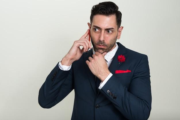 Bello imprenditore barbuto che indossa tuta contro lo spazio bianco