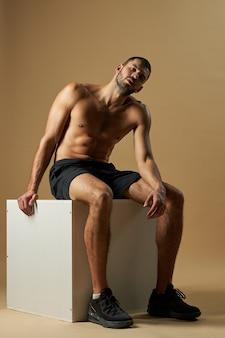 Bel maschio caucasico barbuto in abiti sportivi neri che riposa dopo la pratica in palestra isolata su