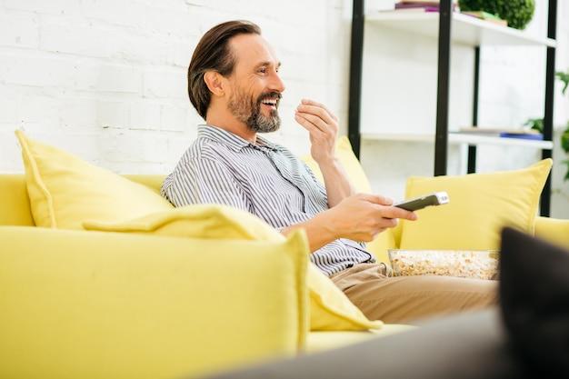 Uomo caucasico barbuto bello seduto comodamente sul divano giallo e sorridente mentre mangia popcorn e utilizza il telecomando per cambiare canale tv