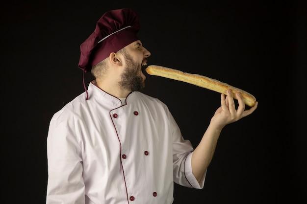 Uomo barbuto bello chef in uniforme morde baguette