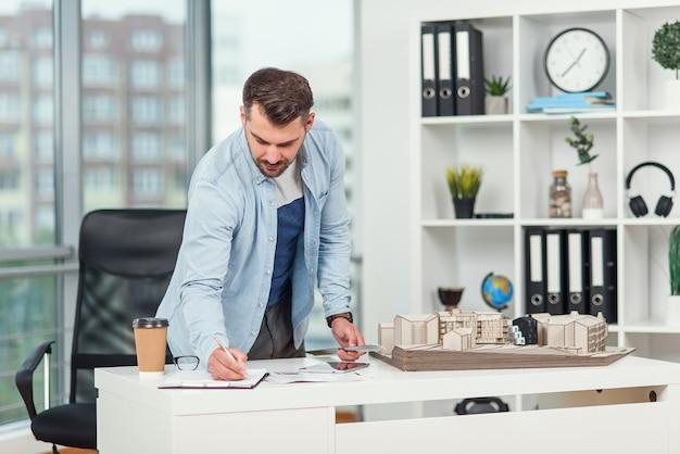 Bel ingegnere barbuto lavora al progetto di costruzione, esamina il modello su cui lavora e annota alcune dimensioni.