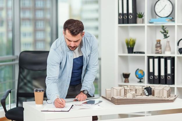 Bel ingegnere barbuto lavora al progetto di costruzione, esamina il modello su cui lavora e