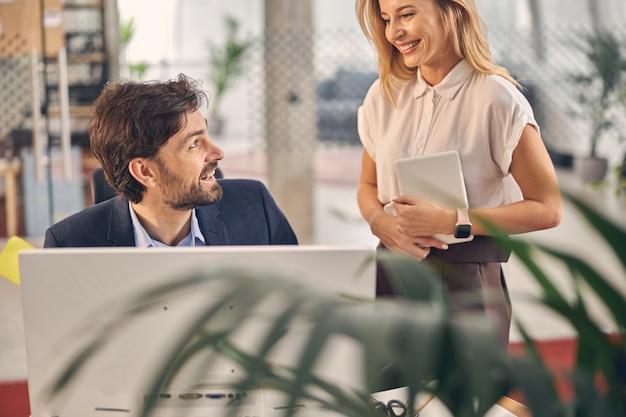Bel gentiluomo barbuto che guarda una signora affascinante e sorride mentre è seduto al tavolo con il computer in ufficio
