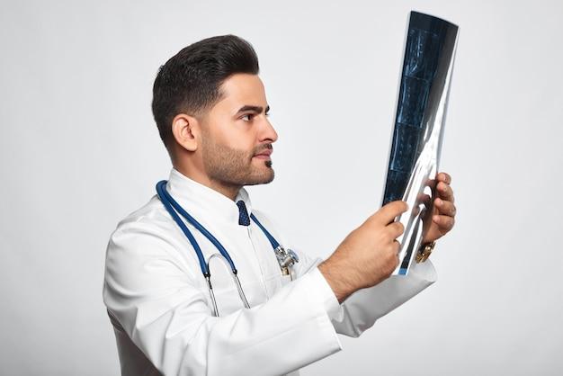 Un bel maschio barbuto medico con uno stetoscopio esaminando la risonanza magnetica sul muro grigio tecnologia medicina indagine medica concetto di professione sanitaria persone.